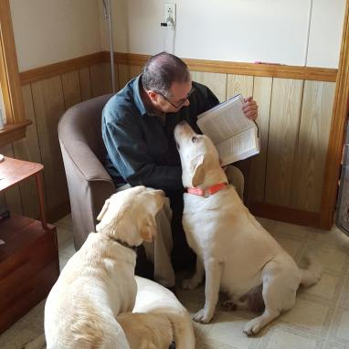 Retired Maine game warden Roger Guay reads his new memoir, A Good Man with a Dog, to Nilla, Saba, and Frisbee
